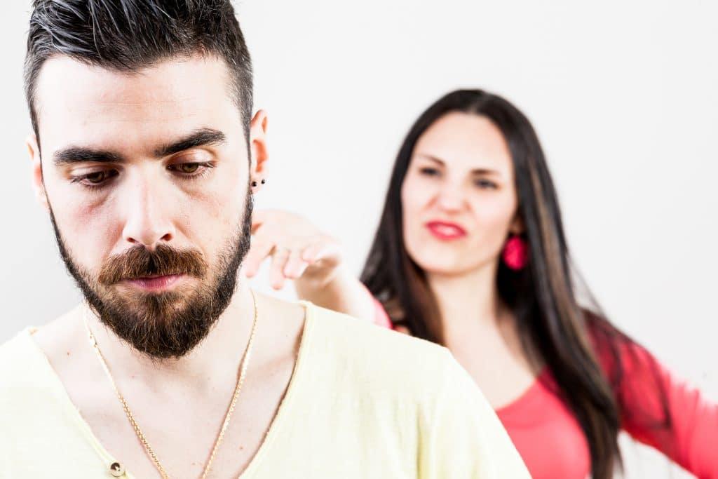 Mulher desprezando o seu esposo. Ela está por trás dele fazendo caretas. Ele está triste.