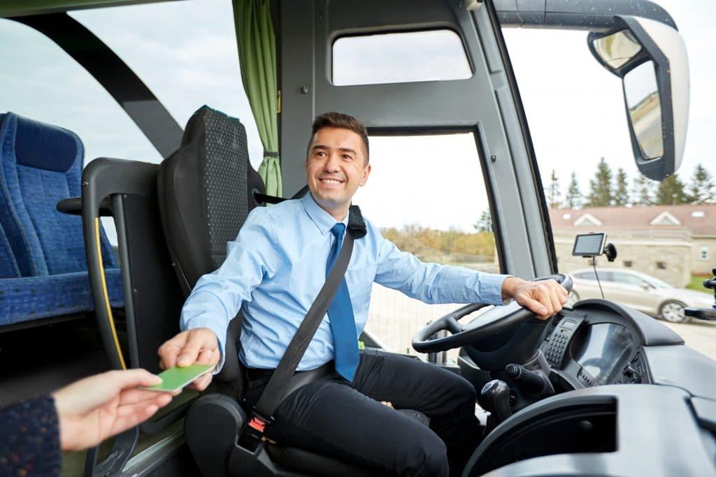Homem sorrindo dirigindo um ônibus. Ele está recebendo a passagem de um dos seus passageiros.