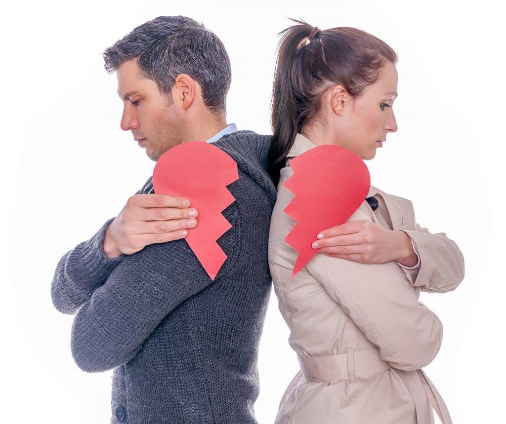 Casal de homem e mulher. Eles estão de costas um para o outro e cada um está segurando metade de um coração de papel.