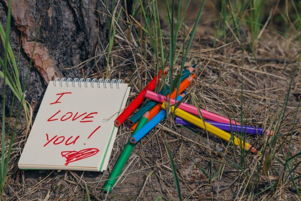 Bloco de anotações para escrever recados de amor. Na capa dele está escrito I Love You. Ao lado do bloco vários lápis coloridos.