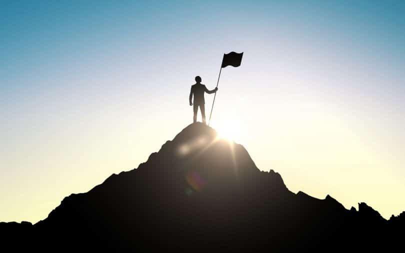 Silhueta de homem em topo de montanha, segurando uma bandeira. Ao fundo, vemos o sol.