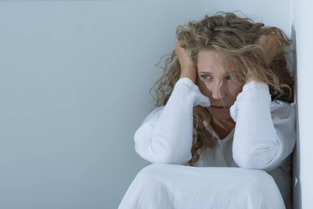 Mulher apreensiva. Ela está sentada encolhida no canto de uma parede. Veste um camisão branco e está com as duas mãos sobre a cabeça.