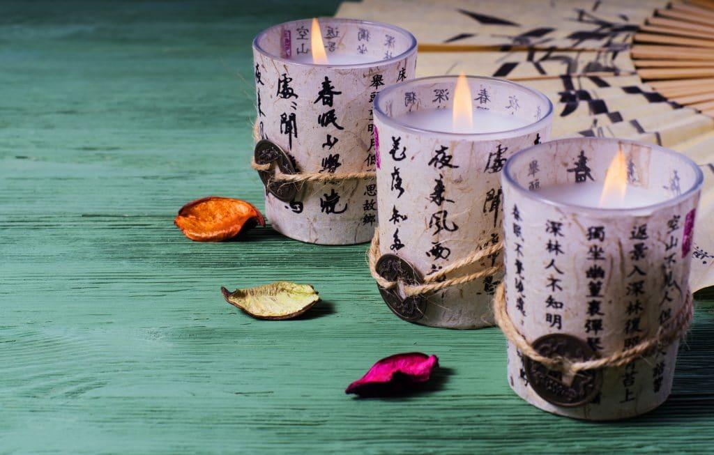Velas em copos decorados com letras chinesas. Os copos estão sobre uma mesa de madeira pintada na cor verde. Ao lado um leque decora os mesmos.