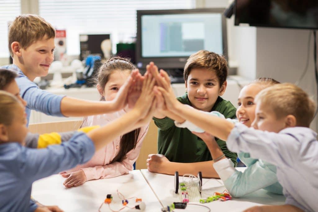 Crianças reunidas dentro de uma sala de aula. Elas estão sentadas em uma mesma mesa, dando as mãos. Sobre a mesa, vários elementos de estudo.