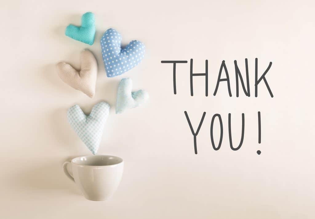 Xícara de café de porcelana na cor branca. Sobre ela quatro corações de feltro nas cores azul e bege. Ao lado temos a palavra THANK YOU escrita em cor preta.