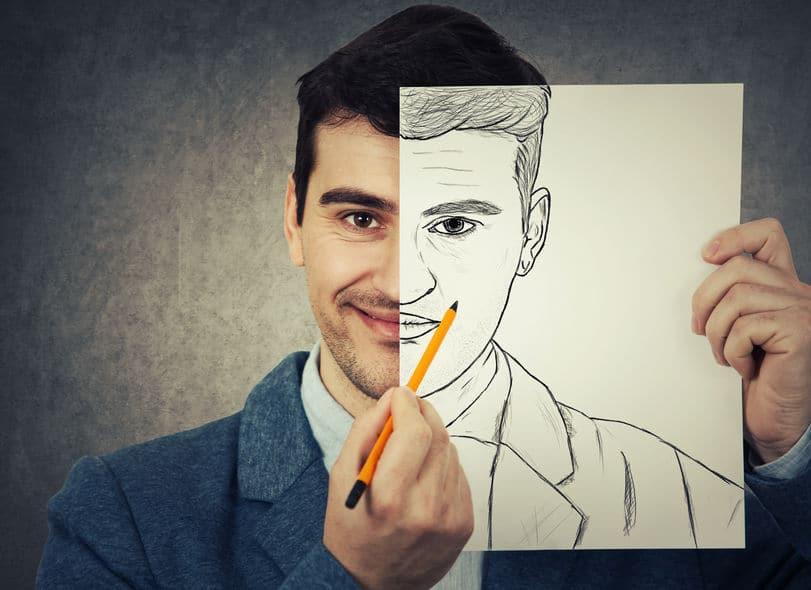 Homem sorrindo, com uma folha de papel cobrindo metade de seu rosto. Nesta folha, vemos um desenho da metade do rosto do rapaz que está coberta.