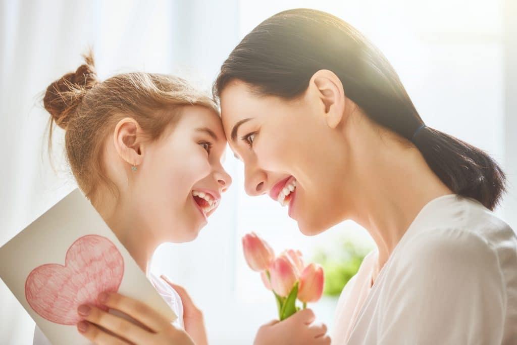 Mãe e filha se abrando e olhando uma para outra com um gesto de muito amor e carinho. A criança oferece um cartão com um coração pintado e um buquê de tulipas rosas.