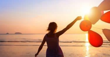 Silhueta de uma mulher na praia, ao pôr do sol, correndo com balões em frente ao mar.