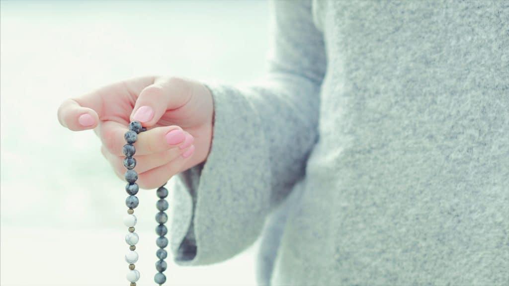 Mão feminina segurando um japamala e fazendo a oração do ho'oponopono.