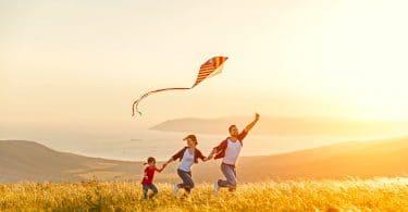 Família correndo em campo com pipa na mão e sol ao fundo