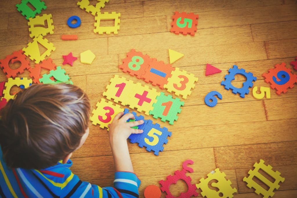 Menino montando quebra-cabeça numérico. São várias peças coloridas em EVA dispostas sobre um piso de madeira,