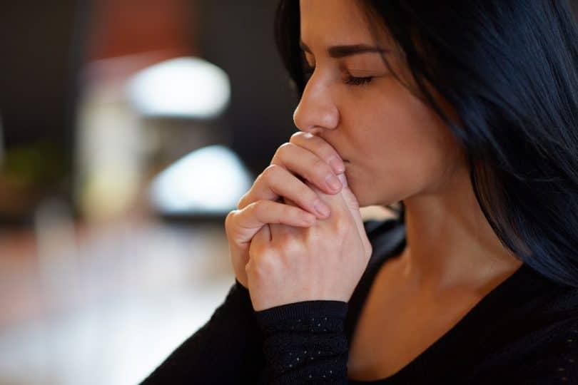 Mulher de olhos fechados e mãos em oração