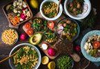 Mesa de madeira com muitas comidas vegetarianas como salada com picles, sanduíche com abacate, macarrão com grão de bico e quinoa.
