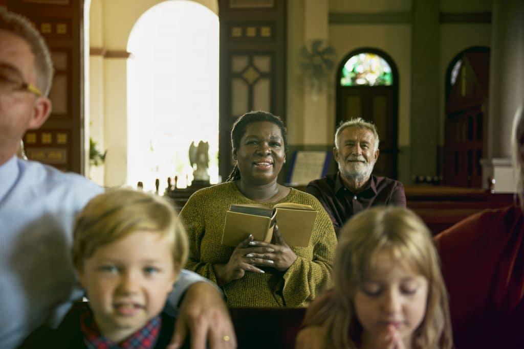 Pessoas e crianças participando de um culto religioso dentro de uma igreja. Uma das pessoas é negra e está segurando a bíblia. Todos na foto estão felizes.