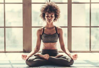 Mulher sentada em posição de meditação com olhos fechados e janelas iluminadas ao fundo