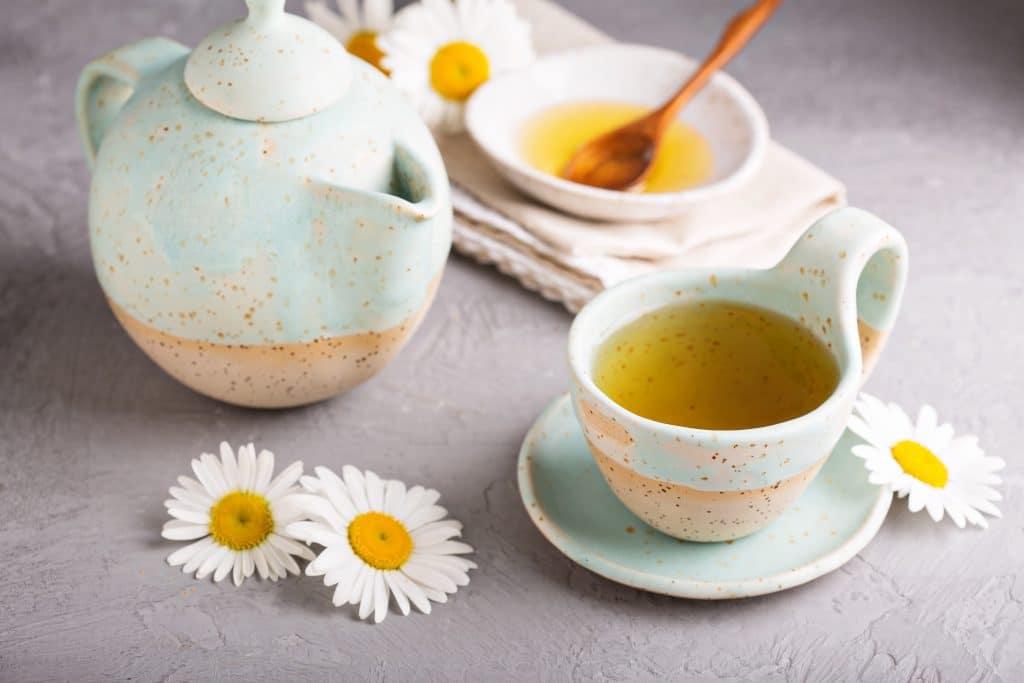 Chá de Melissa servido em uma xícara com pires. Ao lado dela um bule feito com o mesmo material e cor da xícara. Também temos sobre a mesa um recipiente branco com mel para adoçar o chá. Algumas margaridas e uma toalha bege decoram a mesa.