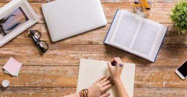 Pessoa estudando em uma mesa com um livro, um caderno, um notebook, quadros e plantas.