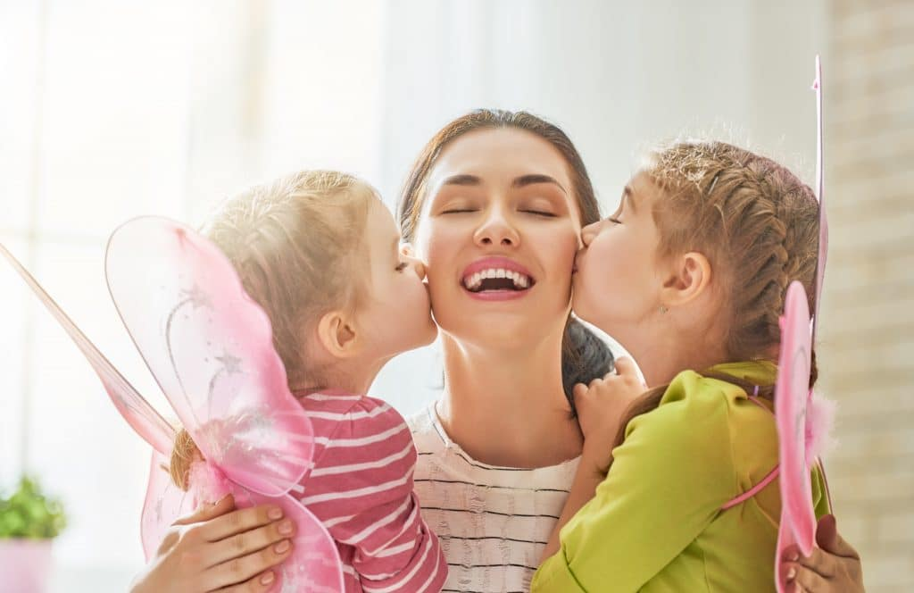 Mãe feliz comemorando o seu dia. Ela está sendo beijada pelas suas duas filhas que estão no seu colo. As crianças usam asas de borboleta na cor rosa.