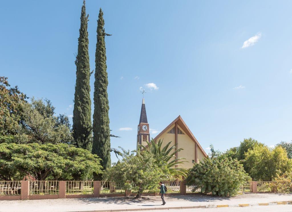 Imagem de uma igreja na cor bege. Ao fundo dela uma torre com um relógio. A igreja está cercada em volta dela temos várias árvores. Na calçada está um homem com uma mochila nas costas.