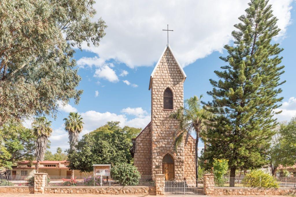 Imagem de  uma igreja construída de pedras. Sobre ela uma cruz. Ela está cercada com grades e um muro baixo feito de pedra. Ao seu redor árvores e um pinheiro bem alto.
