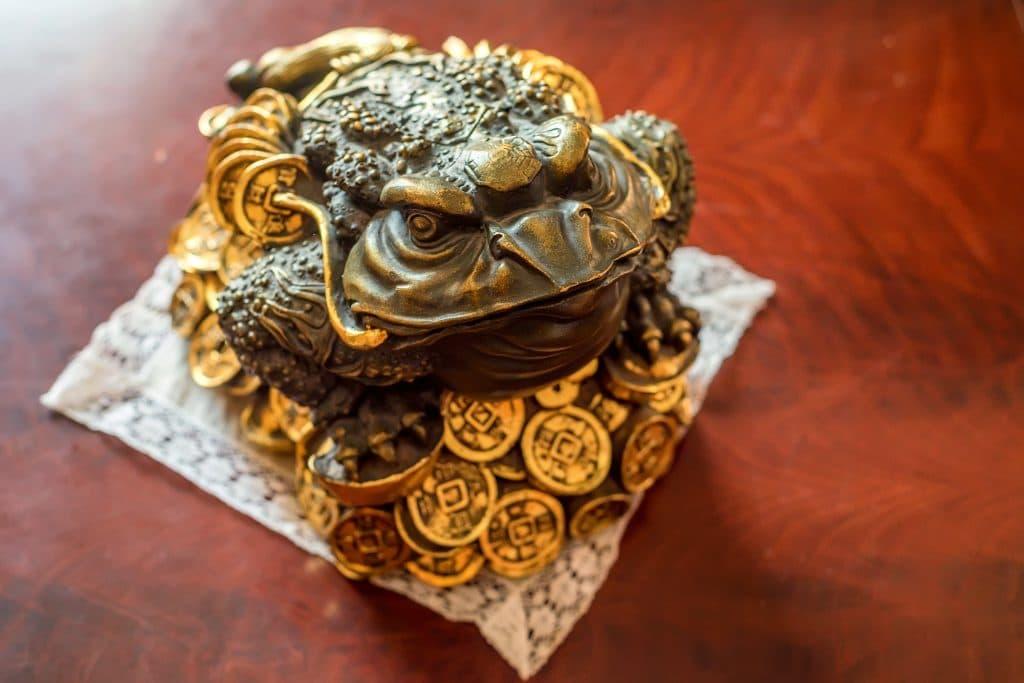 Estátua de sapo de bronze sobre moedas douradas. Trata-se de um souvenir para trazer dinheiro e boas finanças.