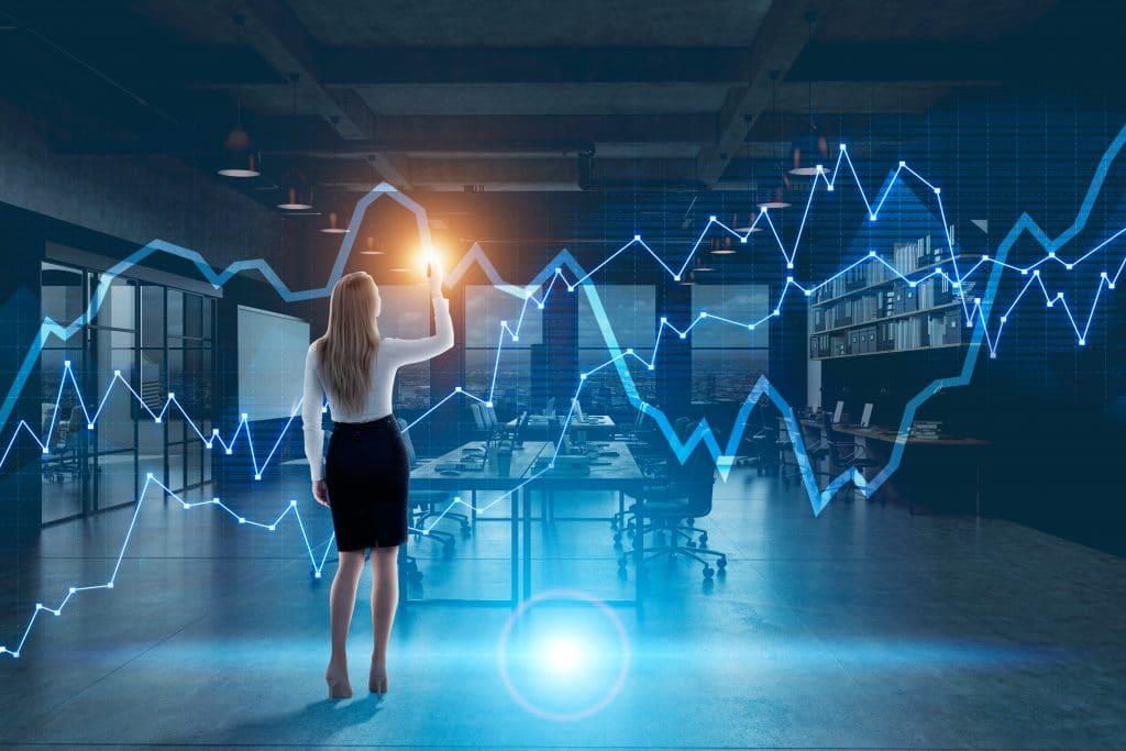 Vista de costas de uma empresária loira desenhando um diagrama holográfico em um escritório à noite.
