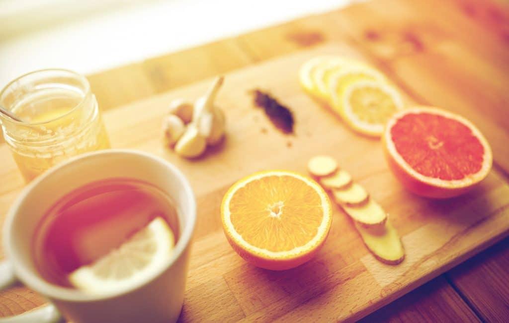 Chá de limão com mel. O chá está sendo servido em uma caneca de porcelana branca sobre uma tábua de madeira. Ao lado dois limões cortados ao meio e em rodela, mel, alho e gengibre compõem os ingredientes da receita.
