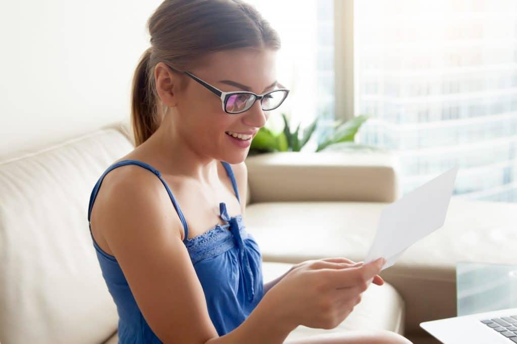 Mulher sentada no sofá da sala. Ela veste uma blusa de alcinha azul e usa óculos de grau. Ela está com o cabelo preso em um rabo de cavalo. Ela está alegre, sorrindo e lendo uma carta com mensagem espírita.