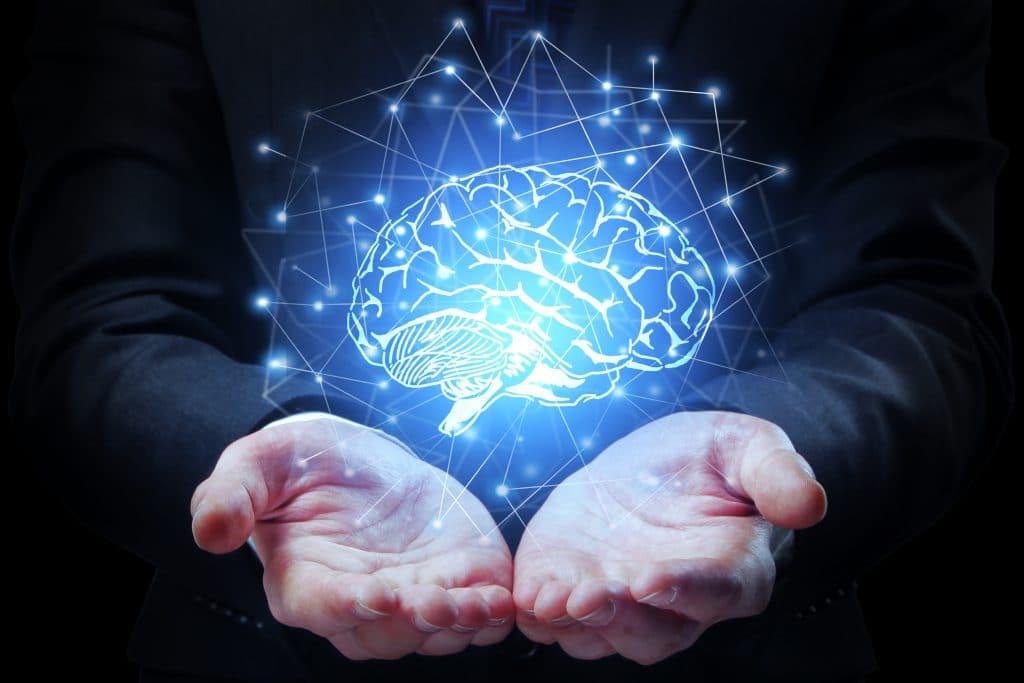Mãos de empresário segurando cérebro abstrato sobre fundo escuro. Conceito de mente artificial