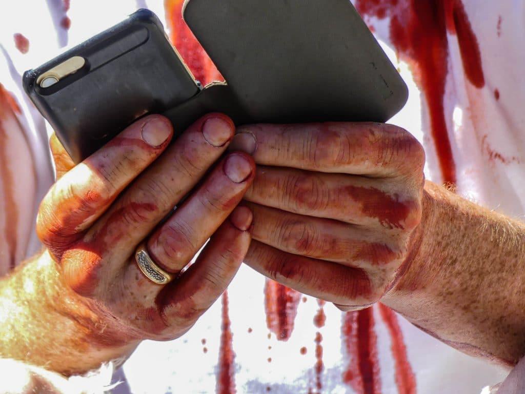 Mãos masculinas sujas com sangue. Ele está segurando entre as mãos um celular.
