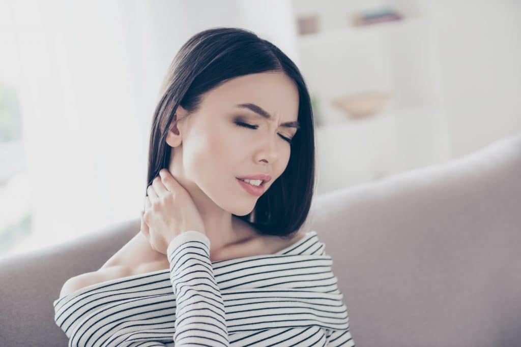 Mulher vestindo uma blusa branca com listras finas na cor preta. Ela está em sua sala, sentada no sofá. Uma das suas mãos está sobre a sua nuca.