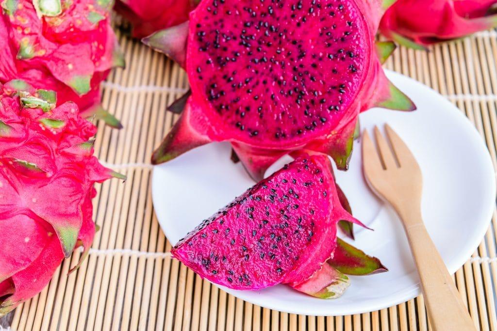 Fruta pitaya corta ao meio e servida sobre um prato de porcelana branco. Ao lado um garfo de madeira. O prato está sobre um suporte feito de madeira bege. Ao lado do prato também temos a fruta inteira.