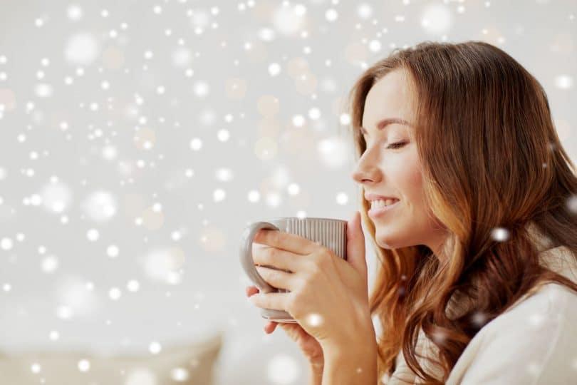 Mulher vista de perfil, com os olhos fechados, bebendo algo quente em uma caneca. Ao fundo, luzes de Natal iluminam o cenário.