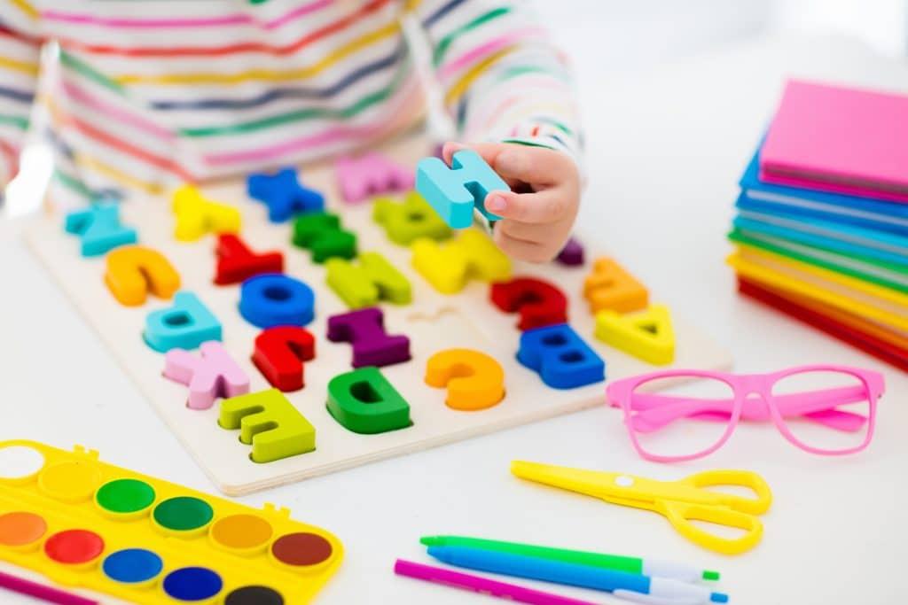 Mãos de uma criança montando um quebra-cabeça de letras coloridas. Sobre a mesa branca estão canetinhas, cadernetas, tesoura, óculos de grau e tinta guache. Tudo com muita cor.