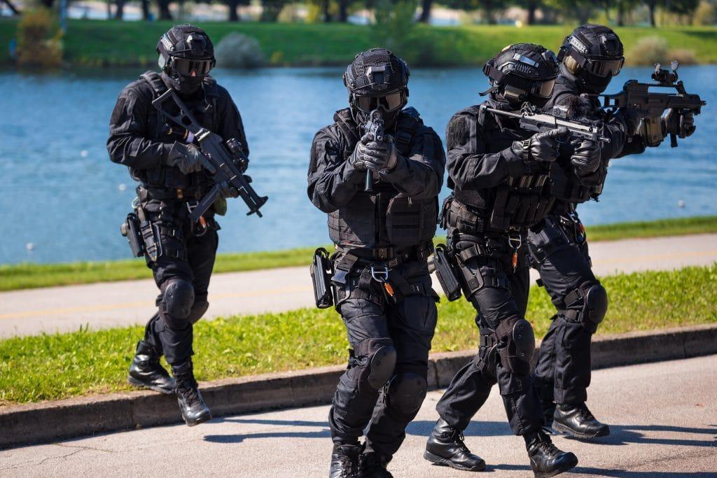 Equipe de quatro policiais da Swat. Todos estão devidamente vestidos com coletes à prova de bala e capacetes. Também estão armados e em posição de ação.