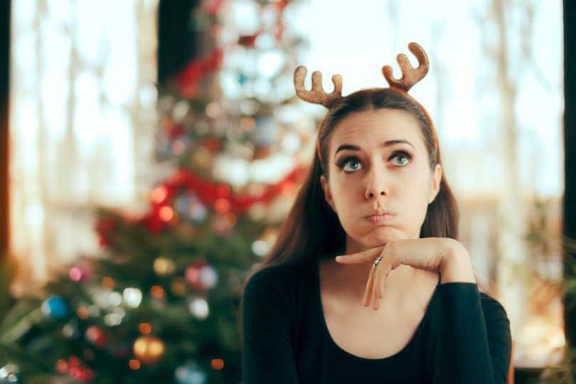 Mulher com arquinho de renas com expressão irritada e árvore de natal ao fundo