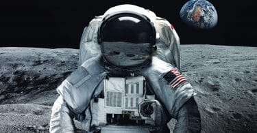 Astronauta com uniforme e bandeira dos Estados Unidos na Lua. Ao fundo é possível ver a Terra.