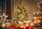 Árvore de Natal decorada ao fundo, e mesa com comida e bebidas para a ceia natalina.