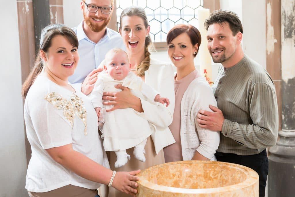 Família reunida para batizado de uma criança. Mãe segura o babê em seu colo e ele veste uma bata branca.