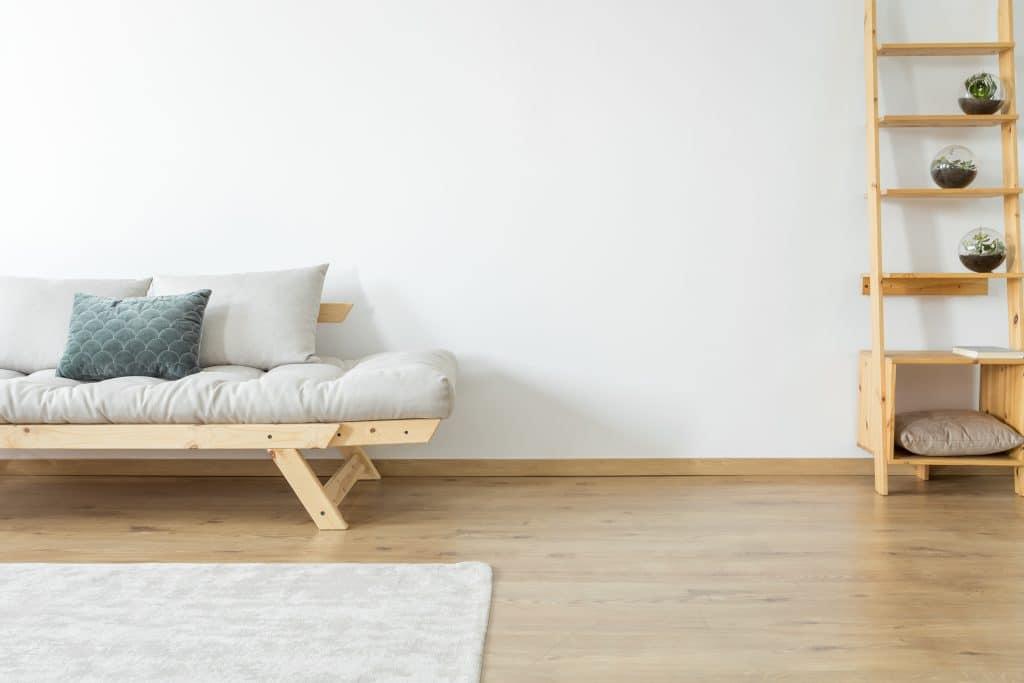 Escada de madeira clara. Ela serve de aparador de vasos de plantas. Ela está disponível em uma sala branca com piso de madeira clara. Ao lado da escada um sofá também de madeira. Ele tem algumas almofadas brancas e uma azul ao centro.