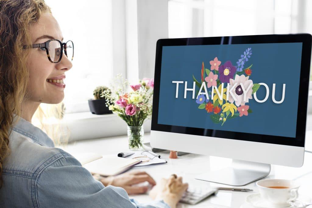 Mulher sorrindo sentada em sua mesa de trabalho de frente para o computador. Na tela do notebook temos um fundo azul com flores onde está escrito a palavra THANK YOU. Sobre a mesa de trabalho temos alguns papéis, canetas e um vaso com flores coloridas.
