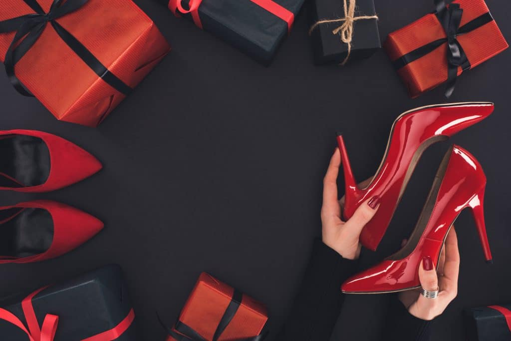 Imagem de uma mão feminina com as unhas pintadas de vermelho. Essas mãos seguram um sapato de salto de verniz na cor vemelha. Ao lado várias caixas de presentes embrulhadas com papel vermelho e preto e decoradas com vitas de cetim nas cores preto e vermelho.
