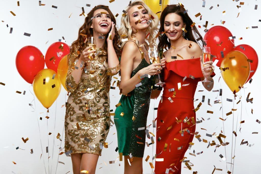 Três lindas mulheres com cabelos longos. Elas usam belos vestidos de festa. Os vestidos são das cores verde, vermelho e dourado. Cada uma delas seguram uma taça de champanhe. Ao lado delas balões coloridos e confetes complementam a imagem.