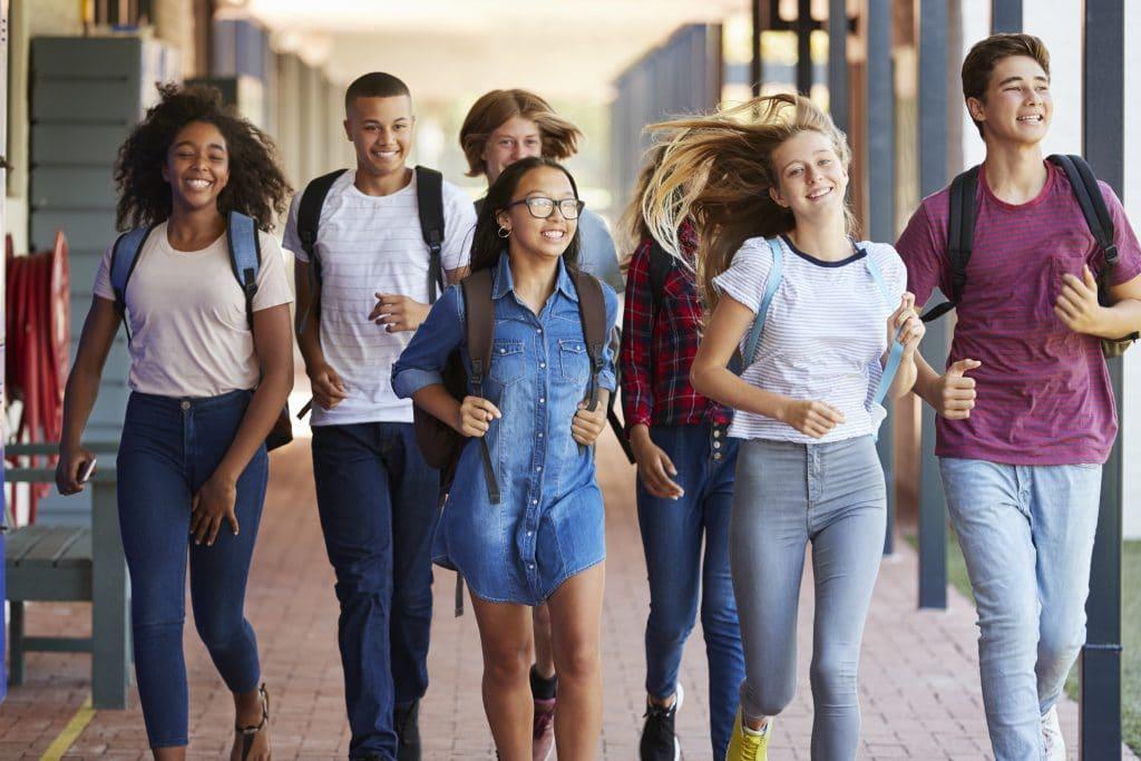 Grupo formado por jovens homens e mulheres de várias etnias. Eles estão com mochilas nas costas, sorrindo e andando no corredor da escola.