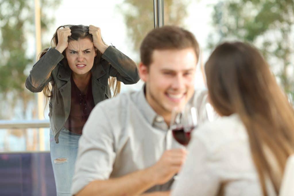 Casal de homem e mulher flertando em um restaurante. Eles estão tomando uma taça de vinho tinto. Ao fundo uma outra mulher preocupada e nervosa olhando para eles. Ela está com as mãos sobre a cabeça. Parece que descobriu a traição do esposo.