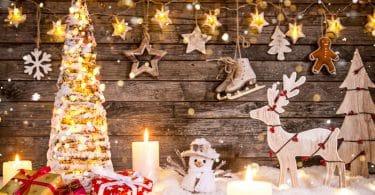 Decoração de Natal toda em miniatura, com árvore iluminada, caixas de presentes, boneco de neve, rena, estrelas e velas.