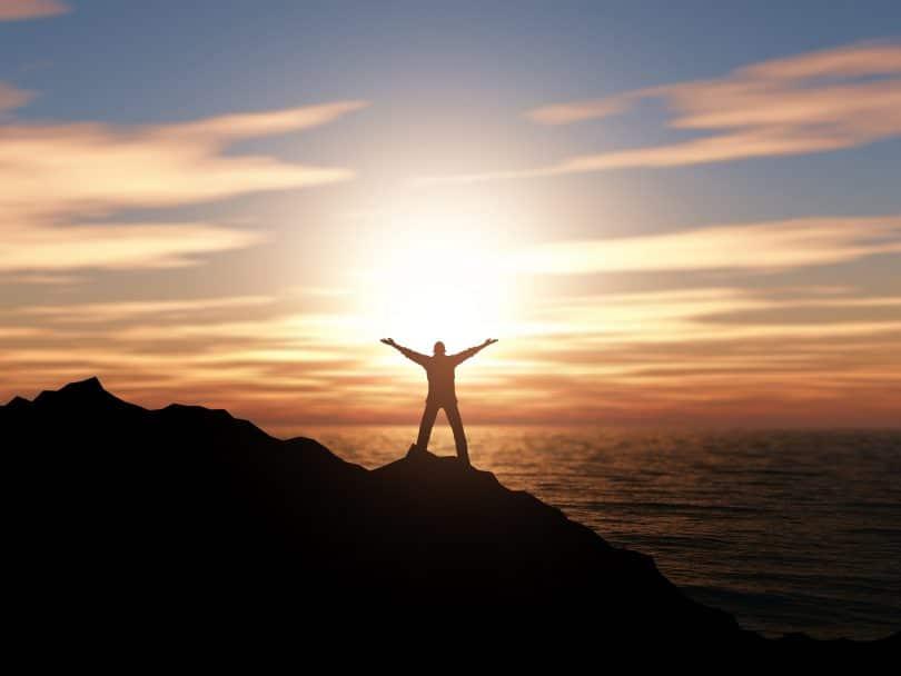 Silhueta de pessoa em cima de montanha com sol ao fundo