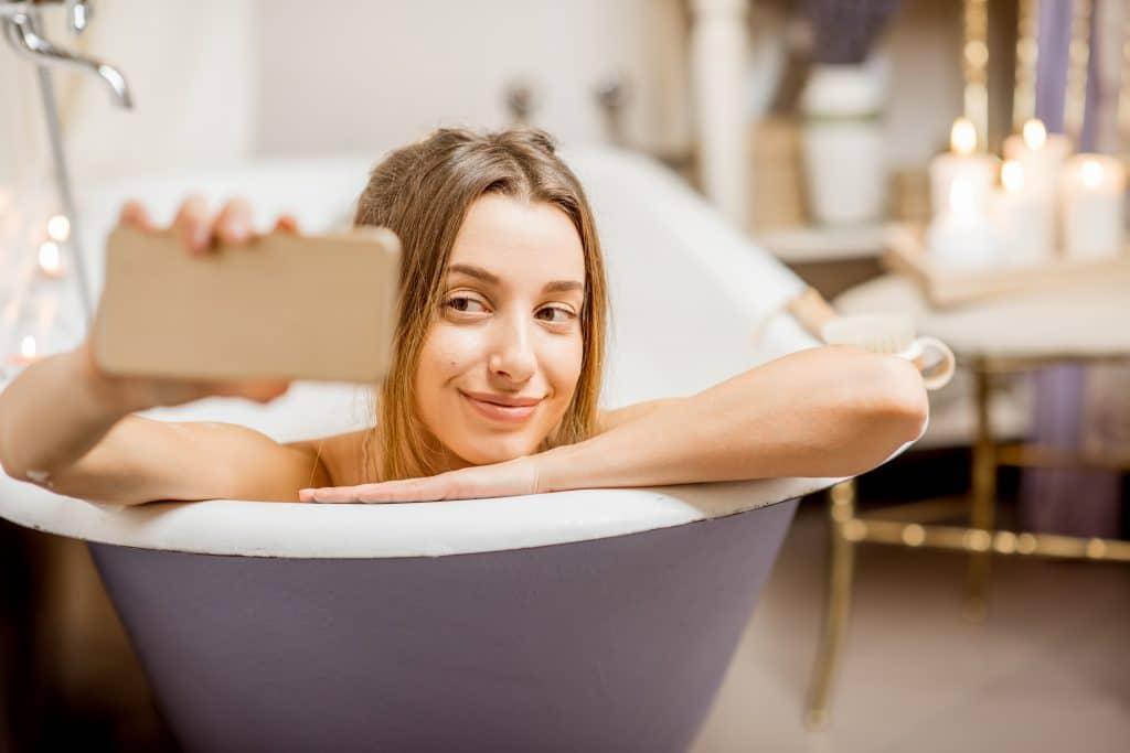 Imagem de uma mulher deitada em uma banheira de bruço com o celular em uma das mãos fazendo uma selfie.