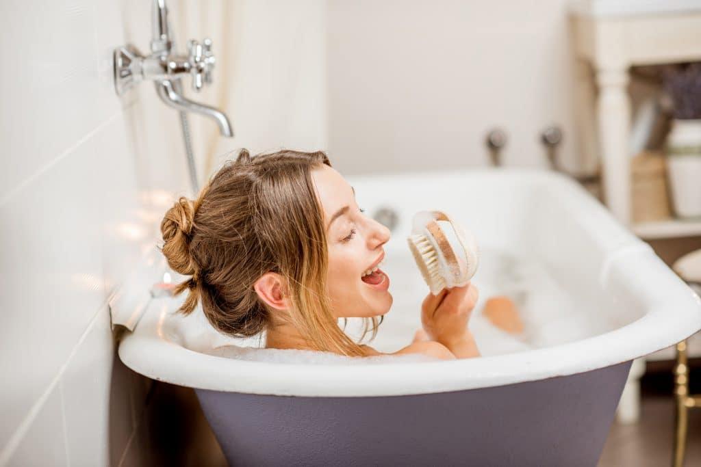 Mulher dentro do banheiro. Ela está em uma banheira cheia de água e sabão. Está tomando banho e segurando sua escova para se esfregar.
