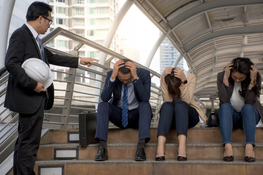 Homem de pé segurando um capacete e apontando o dedo para três pessoas sentadas, sendo duas mulheres e um homem. Os três estão de cabeça baixa com as mãos sobre ela. Eles estão sendo desprezados pelo homem que está de pé.